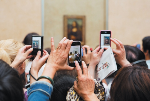 Museumgoers taking photographs of the <i>Mona Lisa</i> at the Louvre, Paris, 2012