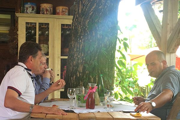 Na kosilu v gostilni Javornik, julija 2016: Andrej Godec nekaj razlaga, Damir Topolko si briše usta, Blaž Miklavčič pa uživa s cigaro.<br>