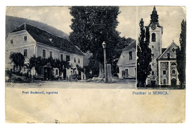 RAZGLEDNICA SEMIČA<br> okoli leta 1910, Semič (Metlika)<br> 9 x 13,9 cm<br> Inv. št.:  R 269<br> <br> Razglednica je bila odposlana 27. decembra 1911 iz Metlike v Ljubljano. Založil jo je trgovec Franc Budkovič, ki je imel v Semiču trgovino z mešanim blagom.