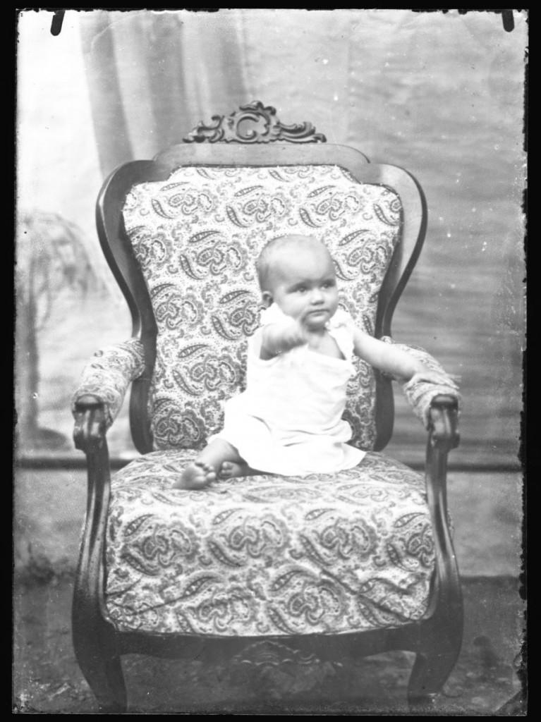 Otrok v naslanjaču<br>Metlika, okoli leta 1910, negativ na stekleni plošči, 16,4 x 11,9 cm<br>inv. št.: Ns 102