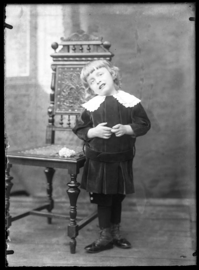 Deklica ob stolu<br>Metlika, okoli leta 1910, negativ na stekleni plošči, 16,4 x 11,9 cm<br>inv. št.: Ns 111