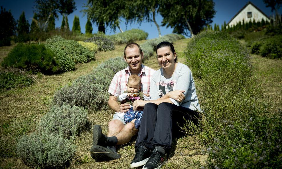 Špela in Boris s sinčkom Florjanom v zeliščnem nasadu na domači kmetiji.
