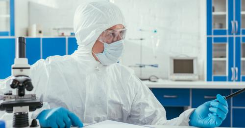 Biochemist in hazmat suit sitting near microscope