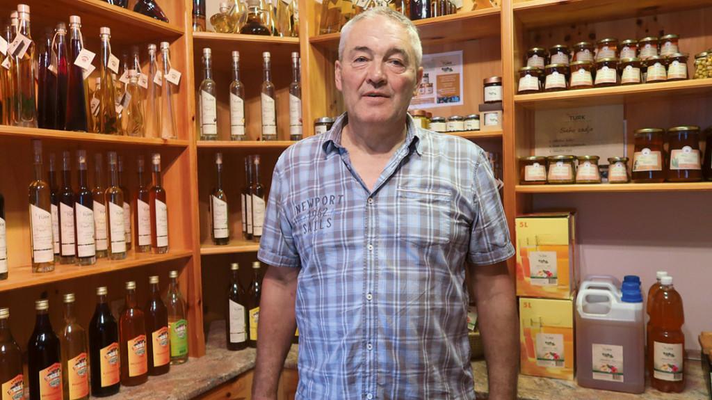 Ivo Turk v prodajalnici na svoji kmetiji s številnimi izdelki iz sadja in medu.