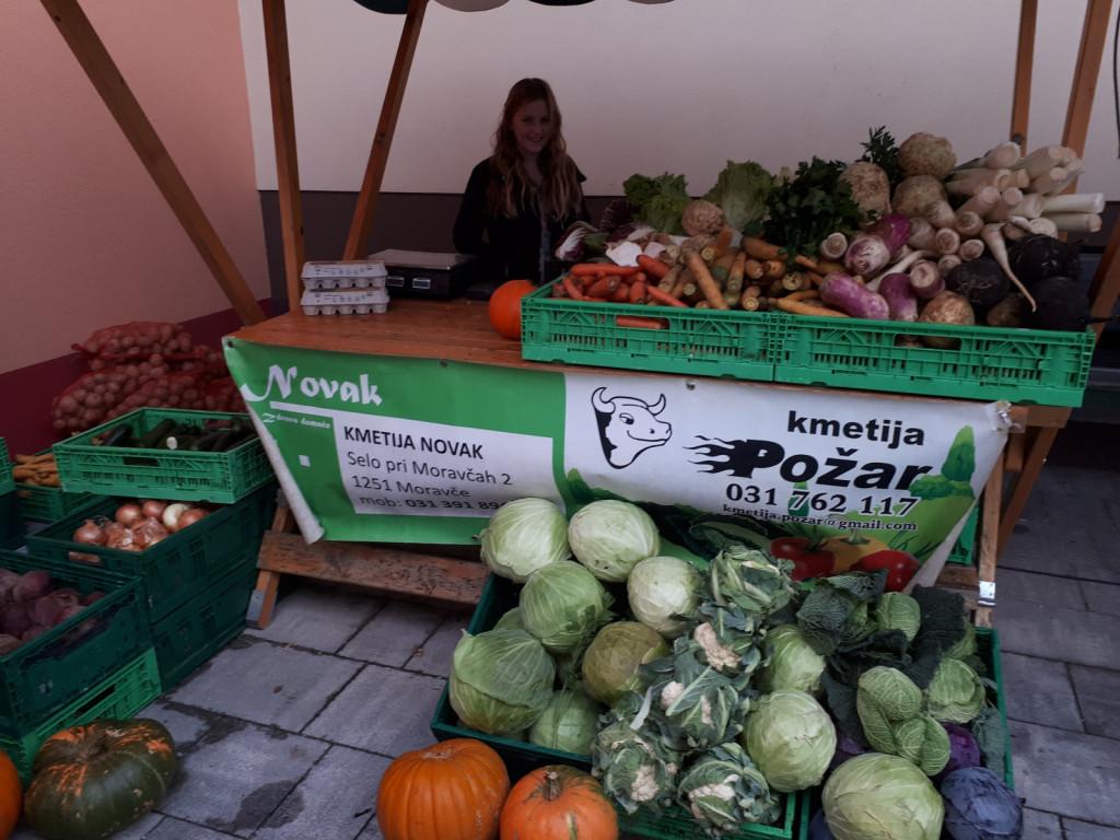 Ajda rada pomaga pri prodaji zelenjave na tržnici v Moravčah.