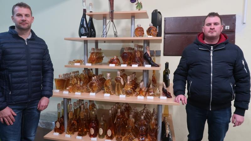 Denis in Kristijan pred stekleničkami z žganjem in likerji . Tradicionalno se ukvarjajo z dopolnilno dejavnostjo žganjekuho, gostje v lični embalaži odnesejo domov vinsko žganje, sadjevec in različne likerje.